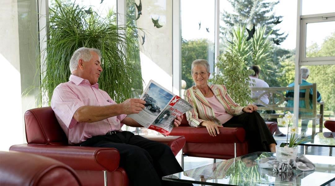 Ehepaar wartet mit zeitung im Anmeldebereich