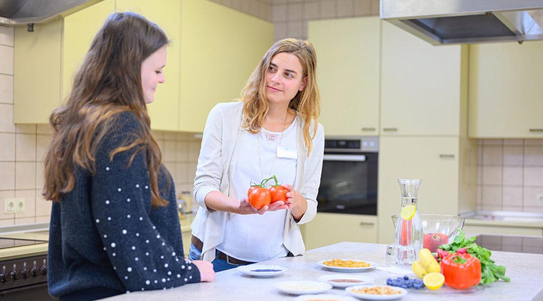 Ernährungsberaterin zeigt Frau Tomaten in der Park Klinik