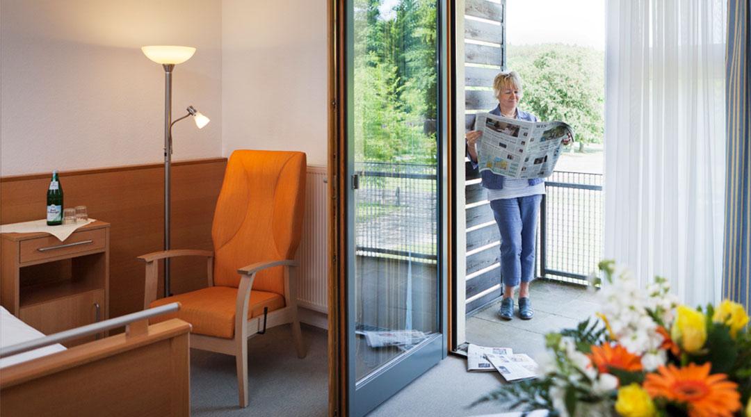 Frau liest auf dem Balkon Ihres Patientenzimmers Zeitung Park Klinik