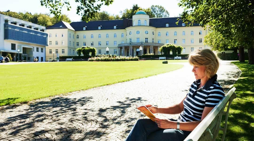 Frau liest vor der Park Klinik ein Buch