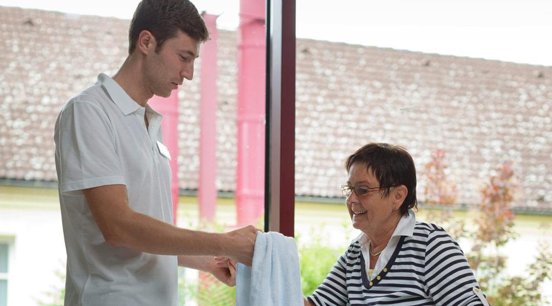 Junger freundlicher Mitarbeiter reicht Dame das Handtuch Park Klinik