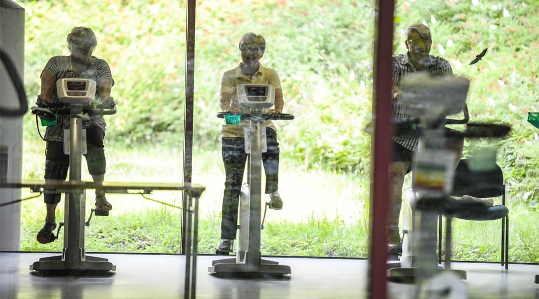 Übungen auf dem Ergometer in der Park Klinik hinter Glassscheibe